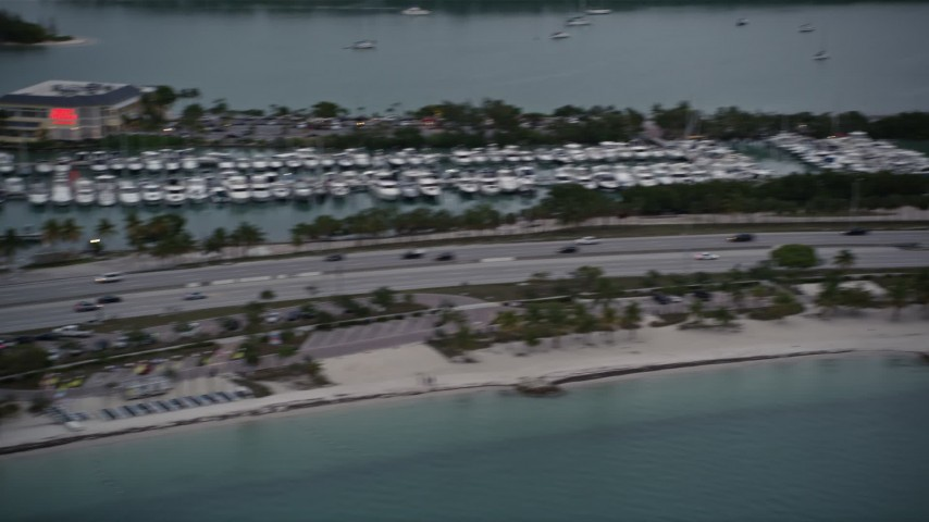 5K stock footage aerial video pan across light traffic on the Rickenbacker Causeway at sunset, Florida Aerial Stock Footage | AX0022_075