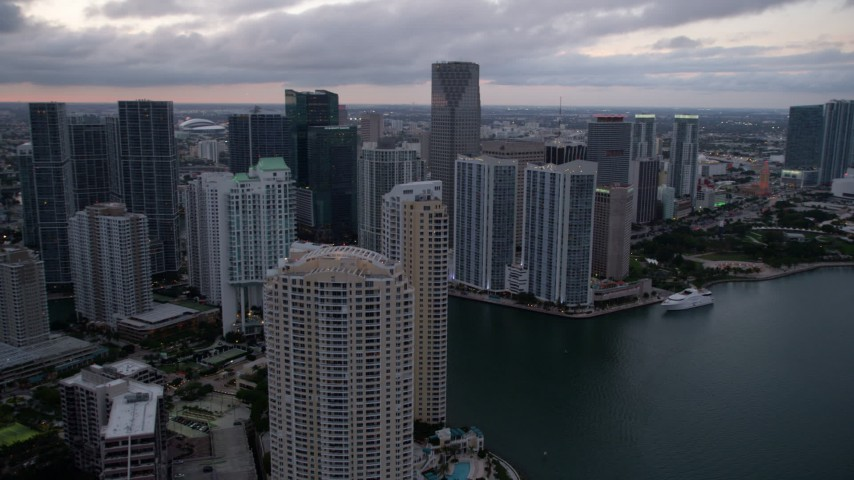 5K stock footage aerial video flyby Brickell Key to reveal skyscrapers by the Miami River at sunset in Downtown Miami, Florida Aerial Stock Footage | AX0022_082