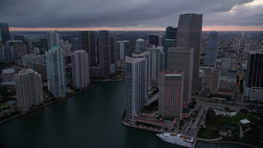 5K stock footage aerial video of passing by the Miami River at sunset to reveal Bayfront Park in Downtown Miami, Florida Aerial Stock Footage | AX0022_084