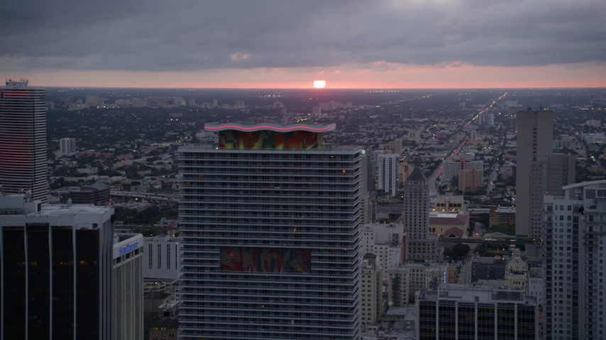 5K stock footage aerial video of setting sun behind 50 Biscayne and Miami Tower in Downtown Miami, Florida Aerial Stock Footage | AX0022_085