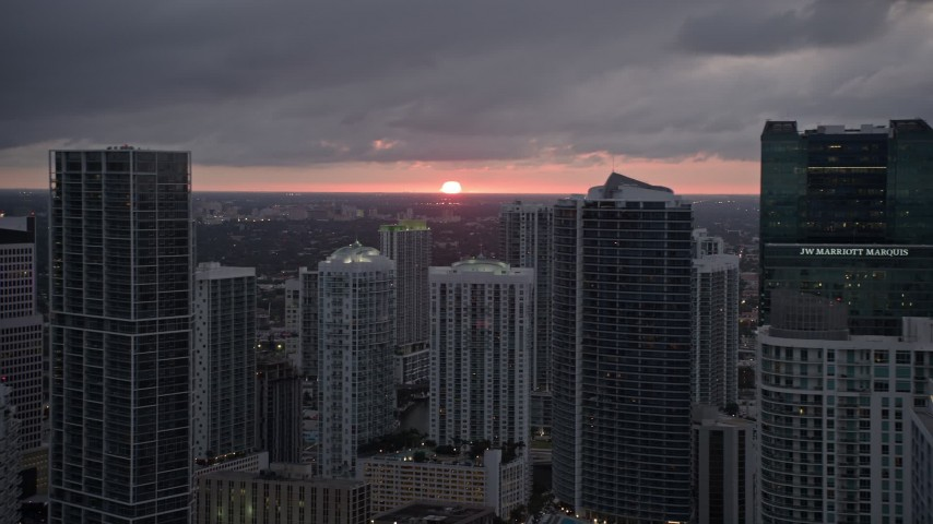 5K stock footage aerial video of setting sun behind tall skyscrapers in Downtown Miami, Florida Aerial Stock Footage   AX0022_085E