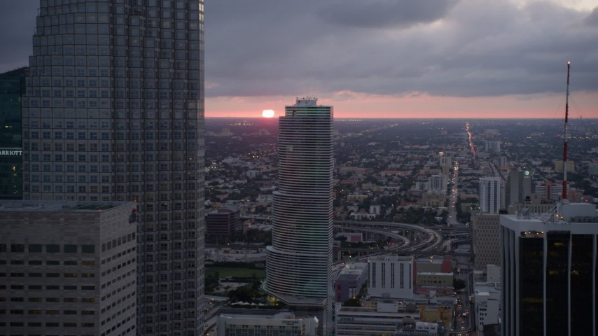 5K aerial video of setting sun in the distance beyond Downtown Miami skyscrapers, Florida Aerial Stock Footage | AX0022_086