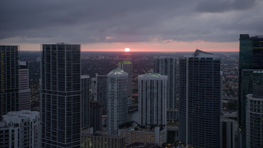 5K stock footage aerial video of setting sun behind Downtown Miami skyscrapers in Florida Aerial Stock Footage   AX0022_087