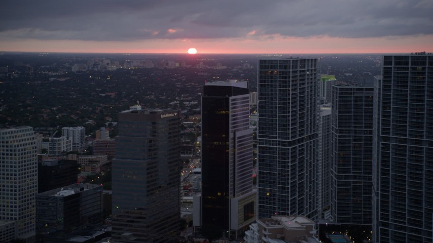 5K stock footage aerial video of the setting sun low on the horizon beyond Downtown Miami skyscrapers, Florida Aerial Stock Footage | AX0022_088