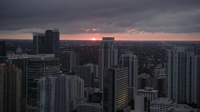 5K stock footage aerial video of the setting sun low on the horizon beyond Downtown Miami skyscrapers, Florida Aerial Stock Footage | AX0022_088E