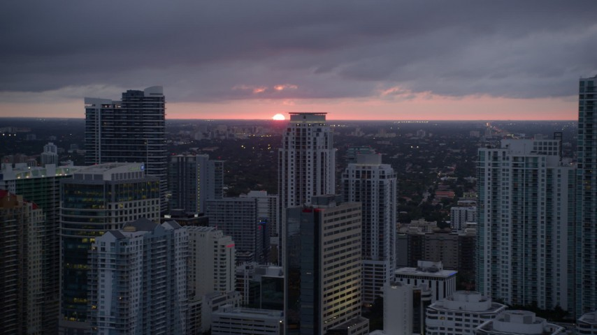 5K stock footage aerial video of setting sun in the distance beyond Downtown Miami skyscrapers, Florida Aerial Stock Footage | AX0022_089