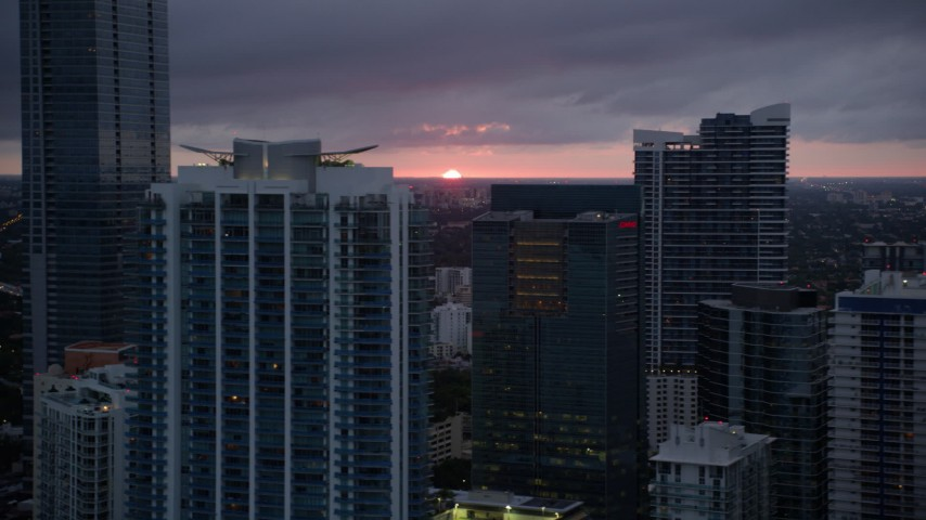 5K stock footage aerial video of Downtown Miami skyscrapers and setting sun on horizon in Florida Aerial Stock Footage AX0022_090 | Axiom Images