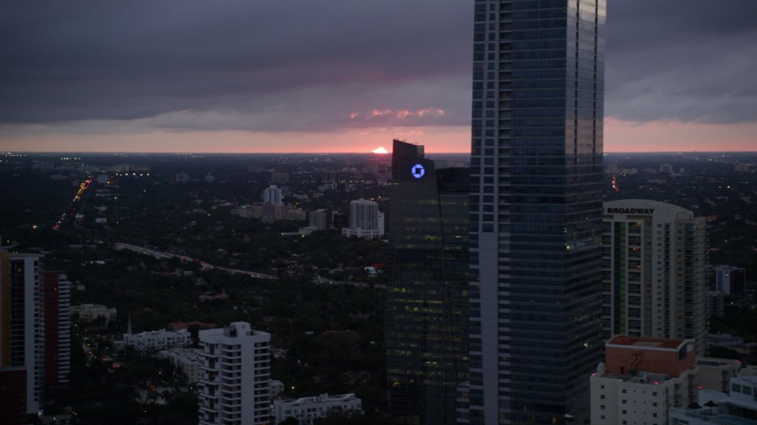 5K stock footage aerial video of low setting sun on the horizon beyond Downtown Miami, Florida Aerial Stock Footage | AX0022_091