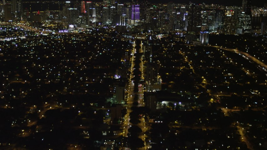 5K stock footage aerial video tilt from SW 3rd Ave to reveal colorful Downtown Miami skyline at night, Florida Aerial Stock Footage | AX0023_003