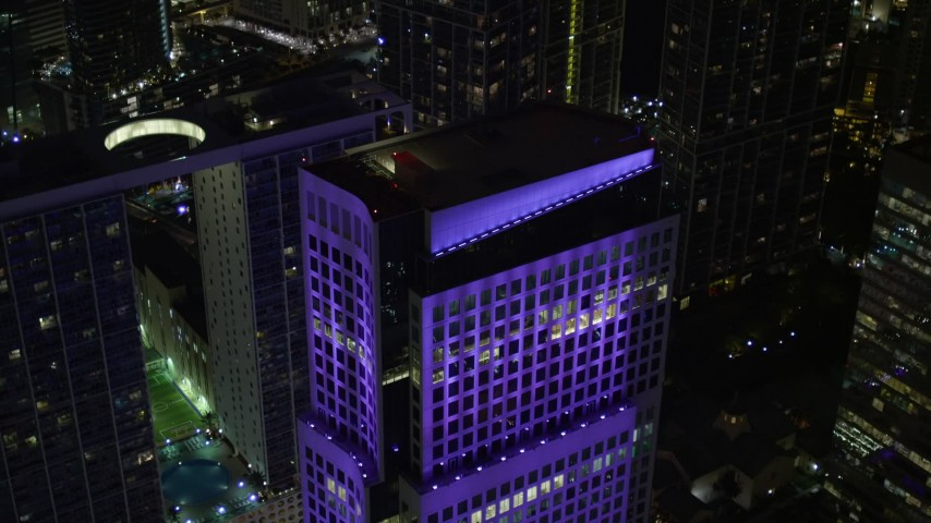 5K stock footage aerial video approach the roof of Brickell World Plaza in Downtown Miami at night, Florida Aerial Stock Footage | AX0023_010E