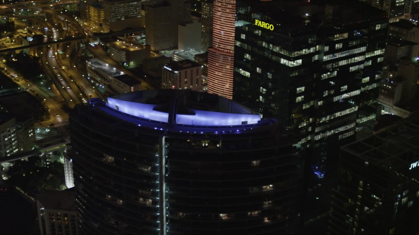 5K stock footage aerial video of orbiting colorful lights on top of Epic Hotel in Downtown Miami at night, Florida Aerial Stock Footage | AX0023_013