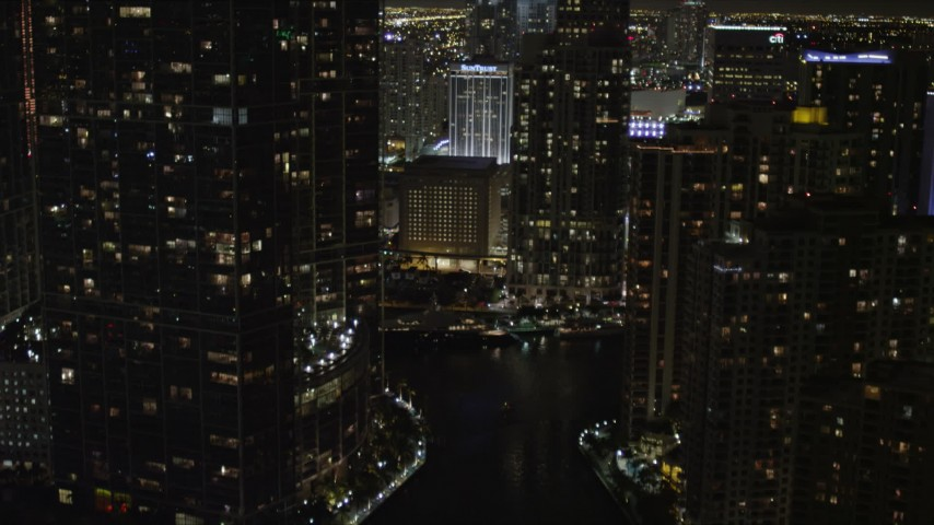 5K stock footage aerial video tilt from bridge to reveal and approach skyscrapers in Downtown Miami at night, Florida Aerial Stock Footage | AX0023_037