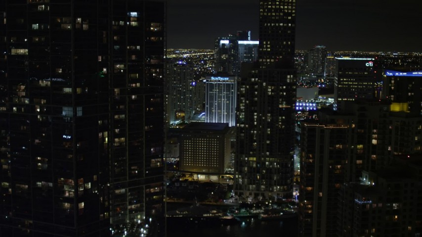 5K stock footage aerial video tilt from bridge to reveal and approach skyscrapers in Downtown Miami at night, Florida Aerial Stock Footage   AX0023_037E