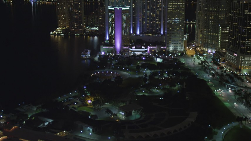 5K stock footage aerial video tilt from Bayside Marketplace to reveal InterContinental in Downtown Miami at night, Florida Aerial Stock Footage | AX0023_045