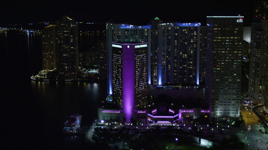 5K stock footage aerial video tilt from Bayside Marketplace to reveal InterContinental in Downtown Miami at night, Florida Aerial Stock Footage | AX0023_045E
