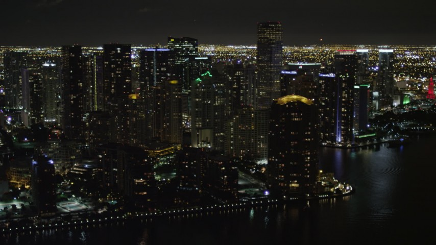 5K stock footage aerial video of flying by high-rises on the shore of Brickell Key at night in Downtown Miami, Florida Aerial Stock Footage | AX0023_057
