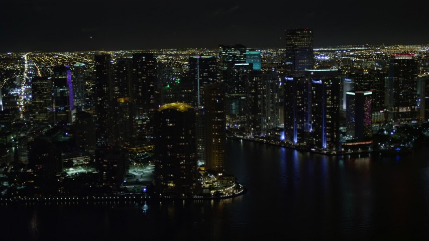 5K stock footage aerial video of flying by high-rises on the shore of Brickell Key at night and reveal river in Downtown Miami, Florida Aerial Stock Footage | AX0023_057E