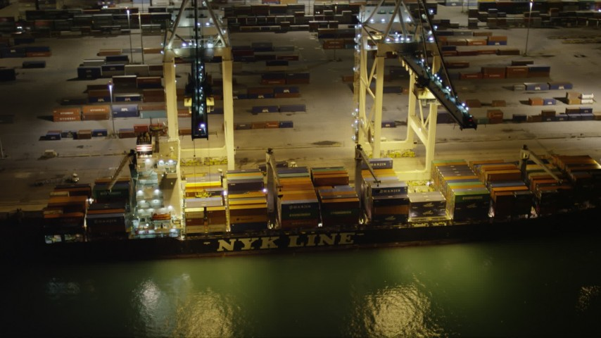 5K stock footage aerial video of cranes unloading a cargo ship docked at the Port of Miami at nighttime, Florida Aerial Stock Footage | AX0023_063