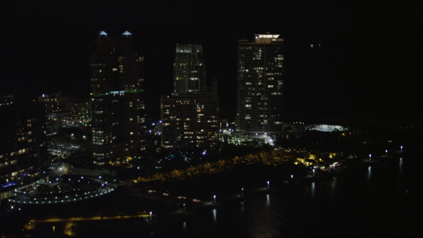 5K stock footage aerial video approach Portofino Tower and skyscrapers in South Beach at night, Florida Aerial Stock Footage | AX0023_065
