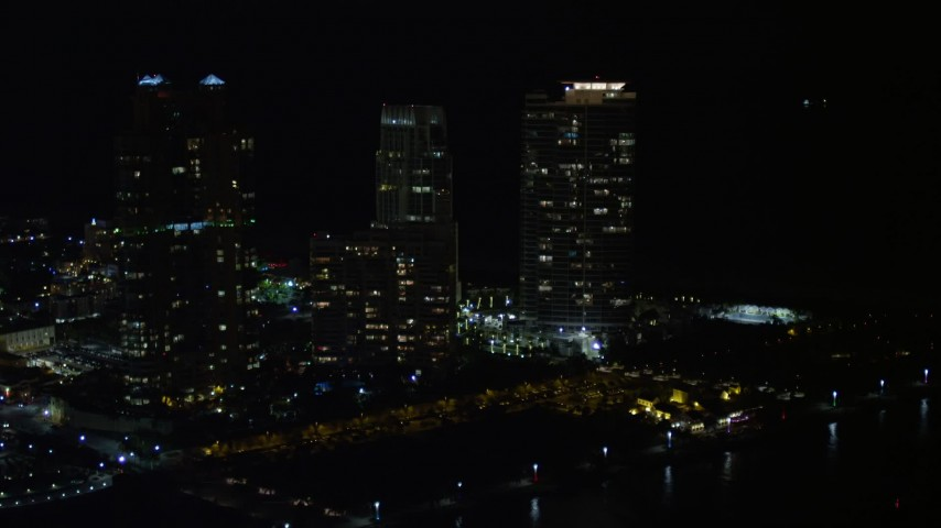5K stock footage aerial video approach and orbit Portofino Tower and skyscrapers in South Beach at night, Florida Aerial Stock Footage   AX0023_065E
