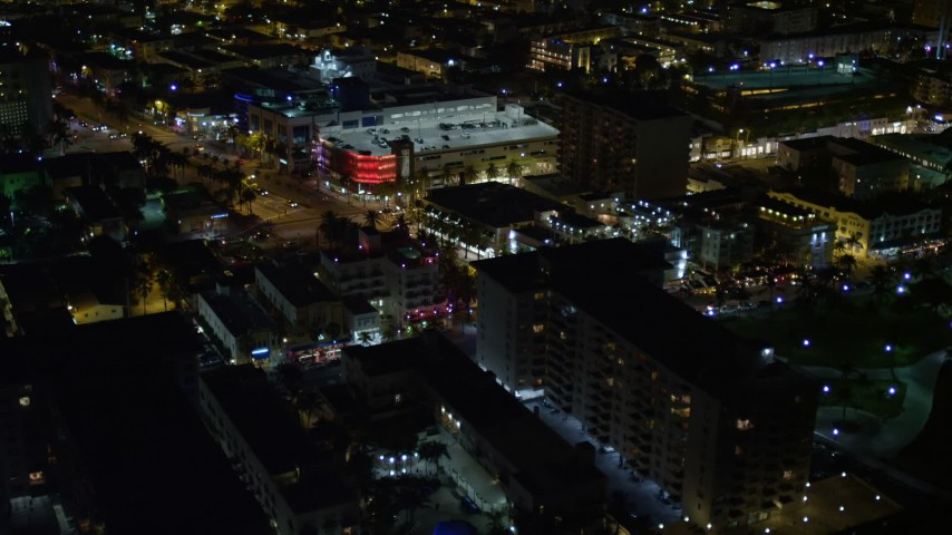 5K aerial video of cafes and shops on an intersection at night in South Beach, Florida Aerial Stock Footage | AX0023_070