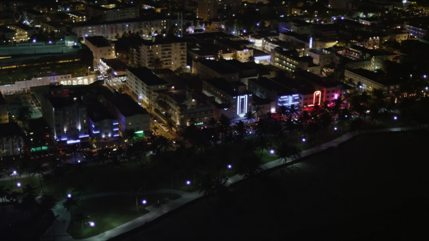 5K stock footage aerial video of hotels and cafes with bright lights at night in South Beach, Florida Aerial Stock Footage | AX0023_071