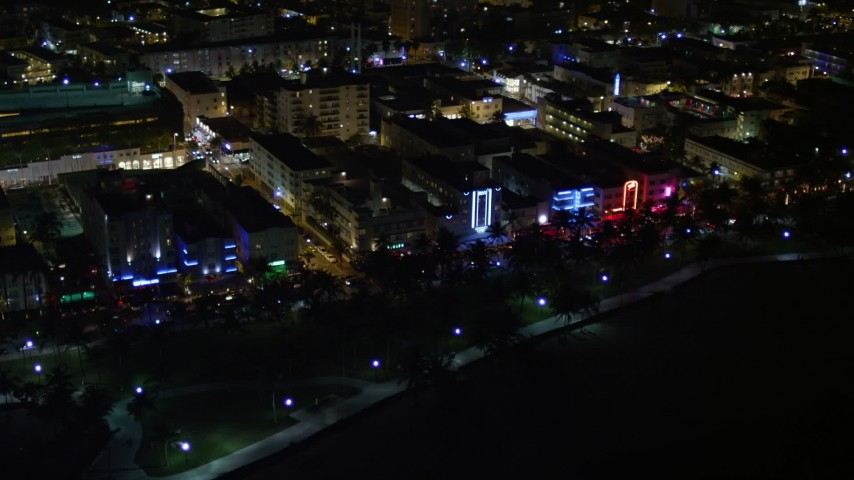 5K stock footage aerial video of hotels and cafes with bright lights at night in South Beach, Florida Aerial Stock Footage | AX0023_071E