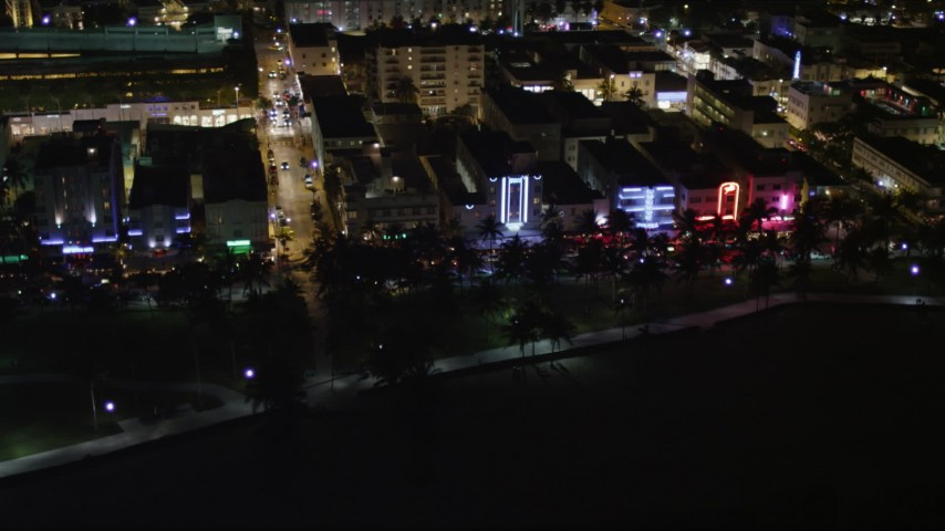 South Beach Hotels and Cafes with Bright Lights at Nighttime Aerial Stock Footage | AX0023_072