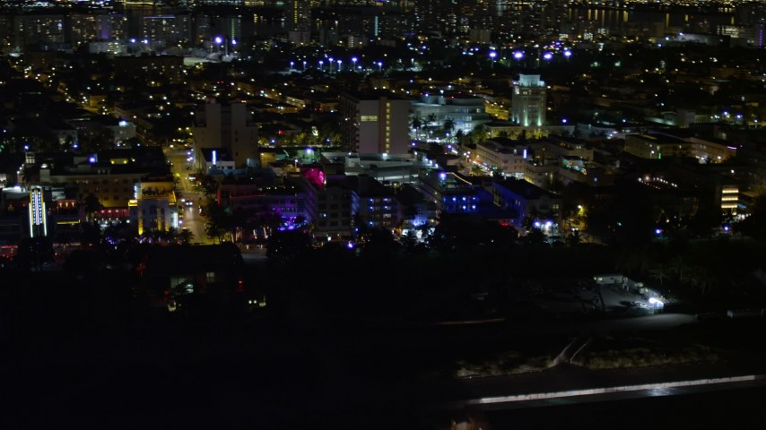 5K stock footage aerial video of Ocean Drive hotels with bright lights at night in South Beach, Florida Aerial Stock Footage | AX0023_073
