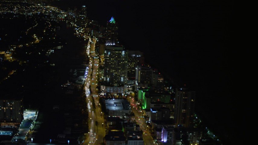 5K stock footage aerial video fly over busy streets through Miami Beach at night, tilt to approach a resort hotel, Florida Aerial Stock Footage   AX0023_083E