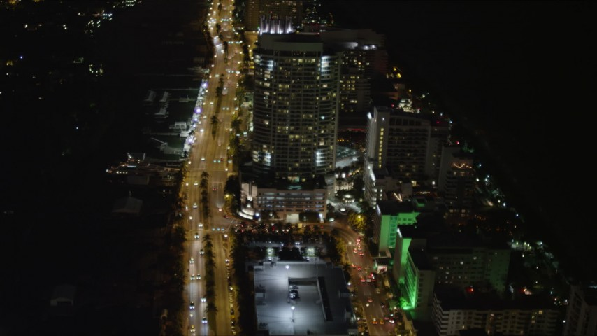 5K stock footage aerial video fly over street by resort hotel at night in Miami Beach, Florida Aerial Stock Footage | AX0023_085