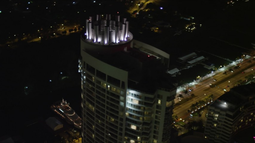 5K aerial video flyby the rooftop of the Fontainebleau Miami Beach Resort Hotel at night, Florida Aerial Stock Footage | AX0023_094