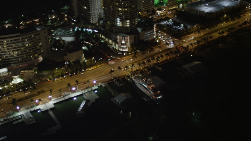 5K stock footage aerial video of a yacht docked by Collins Avenue at night in Miami Beach, Florida Aerial Stock Footage | AX0023_096