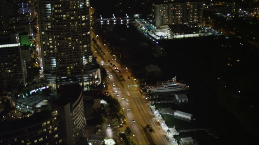 5K stock footage aerial video orbit yacht docked by Collins Avenue and resort hotel at night in Miami Beach, Florida Aerial Stock Footage | AX0023_097