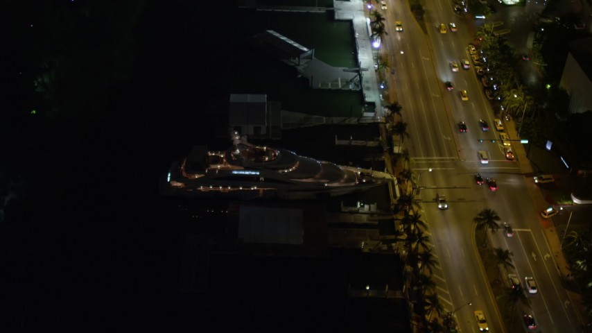 5K stock footage aerial video orbit Fontainebleau Miami Beach Resort Hotel and yacht at night, Florida Aerial Stock Footage | AX0023_098E