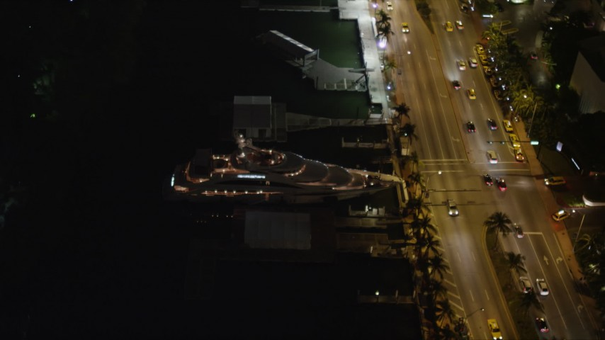 5K stock footage aerial video orbit yacht and Collins Avenue at night in Miami Beach, Florida Aerial Stock Footage | AX0023_100