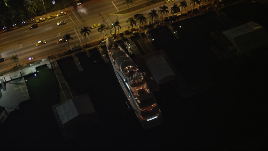 5K aerial video bird's eye view orbit of a yacht docked by Collins Avenue at night in Miami Beach, Florida Aerial Stock Footage | AX0023_101