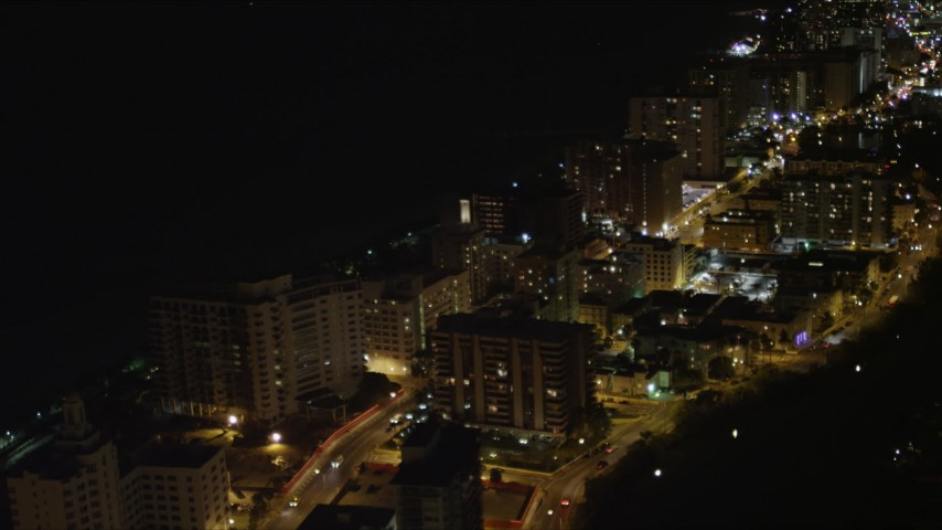 5K stock footage aerial video fly over Miami Beach streets to reveal beachfront condos at night, Florida Aerial Stock Footage | AX0023_103