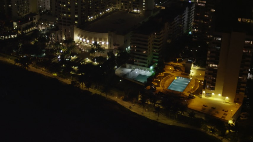 5K stock footage aerial video pan to pools at beachfront hotels at night in Miami Beach, Florida Aerial Stock Footage | AX0023_108