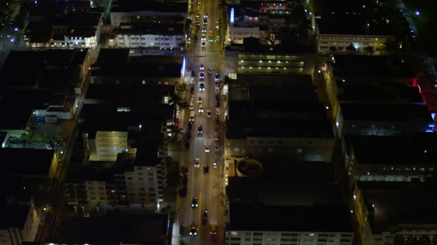 5K stock footage aerial video fly over cars on Collins Avenue at night through South Beach, Florida Aerial Stock Footage | AX0023_114E