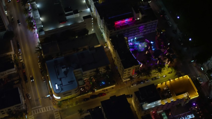 Bird's Eye View of a South Beach Hotel with Bright Lights at Nighttime Aerial Stock Footage | AX0023_116