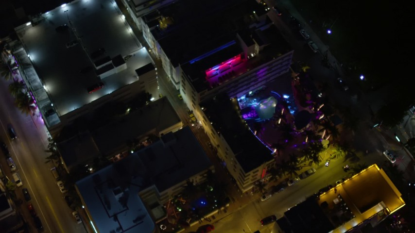 5K stock footage aerial video bird's eye view of a South Beach hotel with bright lights at nighttime, Florida Aerial Stock Footage | AX0023_116