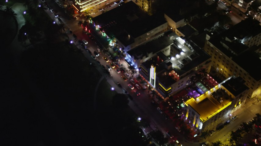 5K stock footage aerial video bird's eye view of Ocean Drive hotels with bright lights at night in South Beach, Florida Aerial Stock Footage | AX0023_122