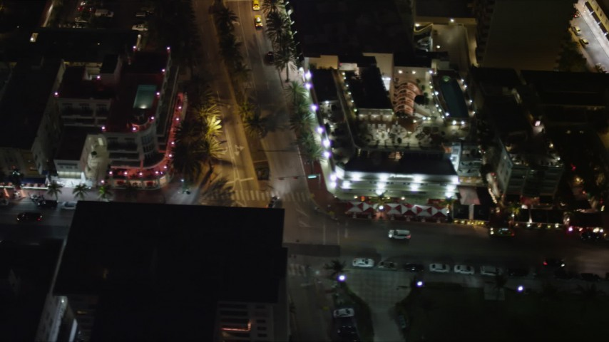 Passing South Beach Hotels on Ocean Drive at Night Aerial Stock Footage | AX0023_125