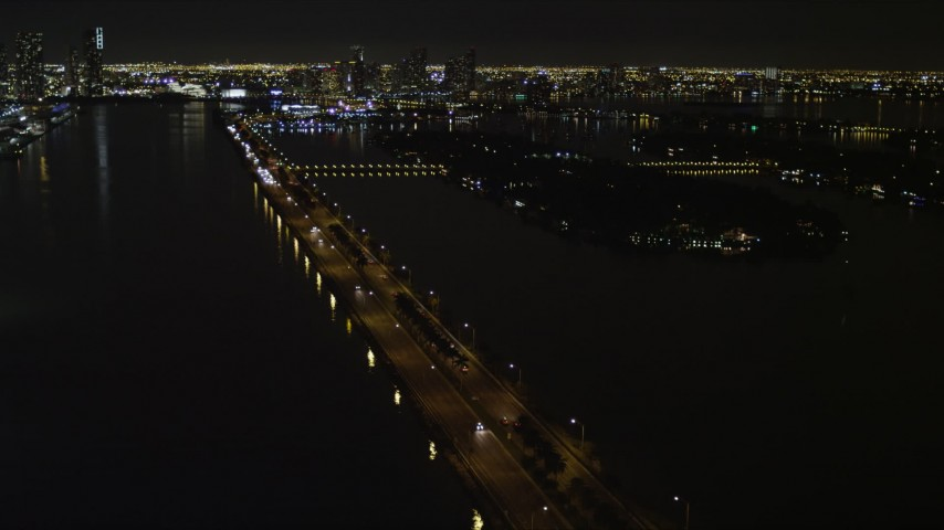 5K aerial video fly over cars traveling on the MacArthur Causeway at night in Miami, Florida Aerial Stock Footage | AX0023_128