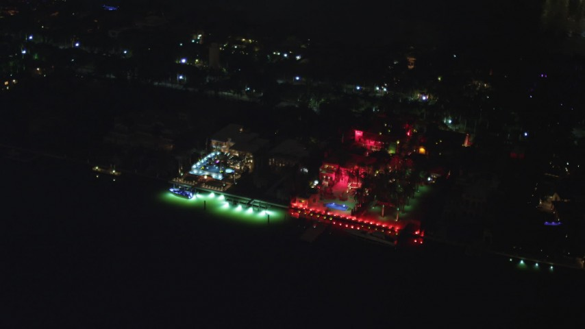 5K stock footage aerial video of 5 Star Island Hotel with bright red lights at night in Florida Aerial Stock Footage | AX0023_130