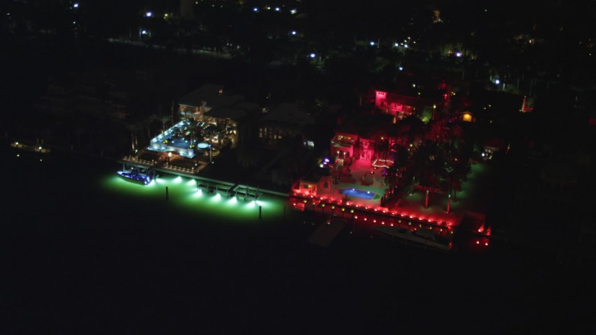 5K stock footage aerial video flyby a waterfront hotel on Star Island with bright red lights at night in Florida Aerial Stock Footage | AX0023_132
