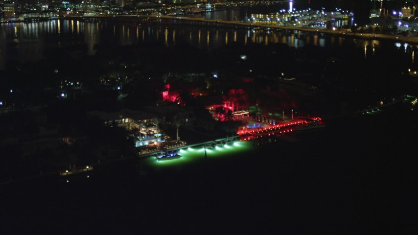 5K stock footage aerial video fly away from bayfront Star Island hotel with red lights at night in Florida Aerial Stock Footage | AX0023_133