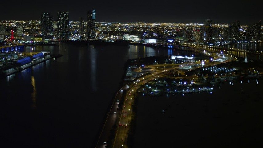 5K stock footage aerial video tilt from the MacArthur Causeway to reveal skyscrapers in Downtown Miami at night in Florida Aerial Stock Footage | AX0023_135
