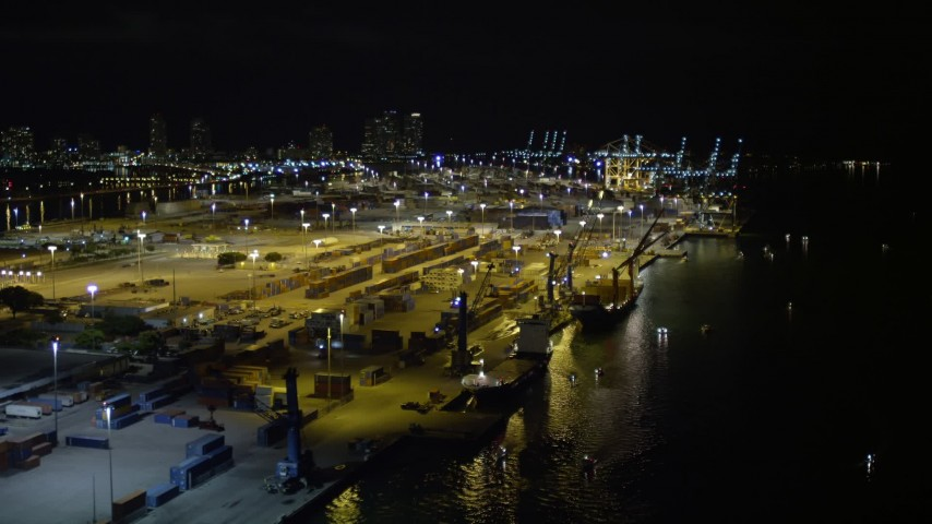 5K stock footage aerial video of passing cargo ships docked beneath cranes at the Port of Miami at night, Florida Aerial Stock Footage | AX0023_152